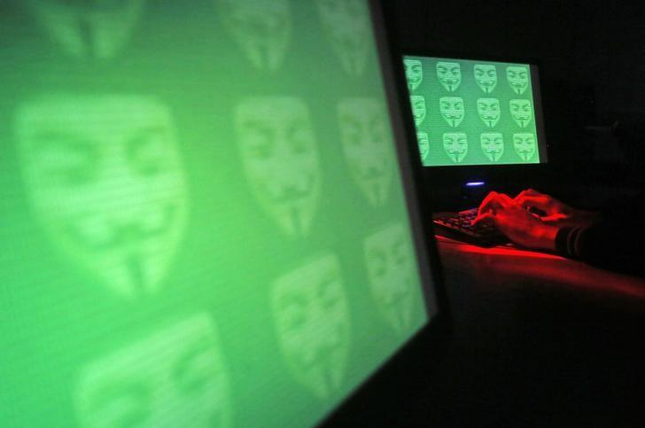 Man poses in front of on a display showing the word 'cyber' in binary code, in this picture illustration taken in Zenica December 27, 2014. REUTERS/Dado Ruvic/files
