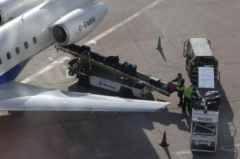 Baggage handlers load luggage onto an aircraft at Manchester Airport, northern England February 3, 2011. REUTERS/Phil Noble