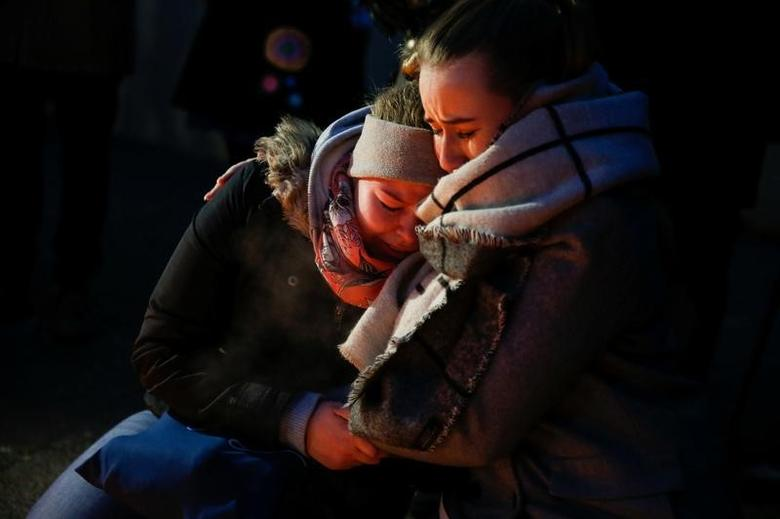 Women mourn at the scene where a truck ploughed into a crowded Christmas market in the German capital last night in Berlin, Germany, December 20, 2016 REUTERS/Fabrizio Bensch