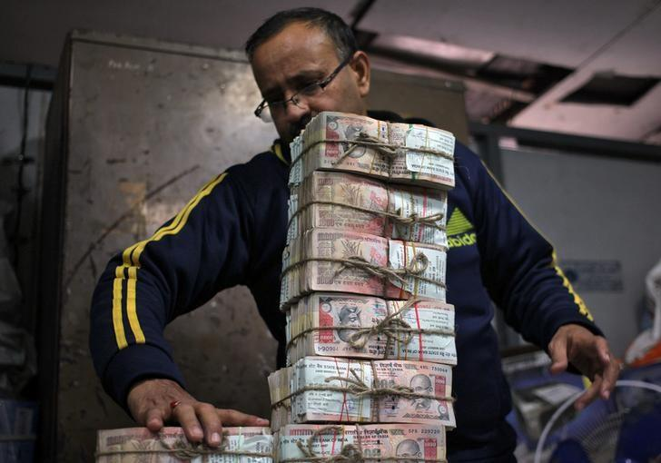 A bank employee stacks a bundle of old 1000 Indian rupee banknotes to count them inside a bank in Jammu, November 25, 2016. REUTERS/Mukesh Gupta
