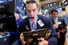 Трейдеры на Уолл-стрит. Индексы США практически не изменились в начале торгов среды, а Dow Jones по-прежнему находится в непосредственной близости от ускользающей отметки в 20.000 пунктов день спустя после того, как он и Nasdaq Composite обновили рекордные максимумы. REUTERS/Brendan McDermid