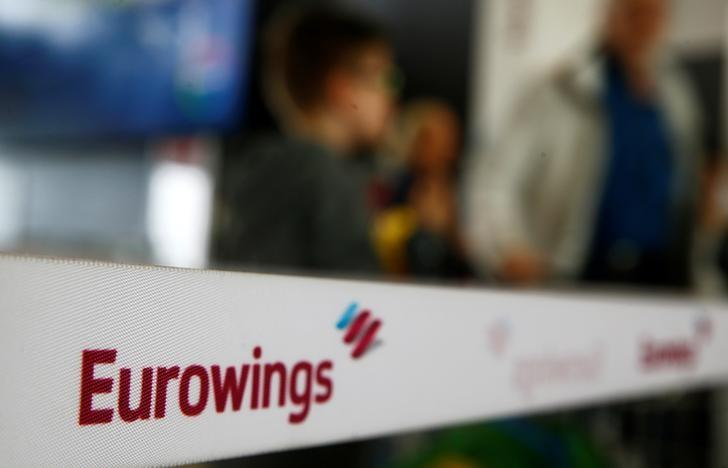 People line up behind a barrier tape of Lufthansa's budget airlines Eurowings during a 24-hour strike over pay and working conditions at Cologne-Bonn airport, Germany October 27, 2016.   REUTERS/Wolfgang Rattay