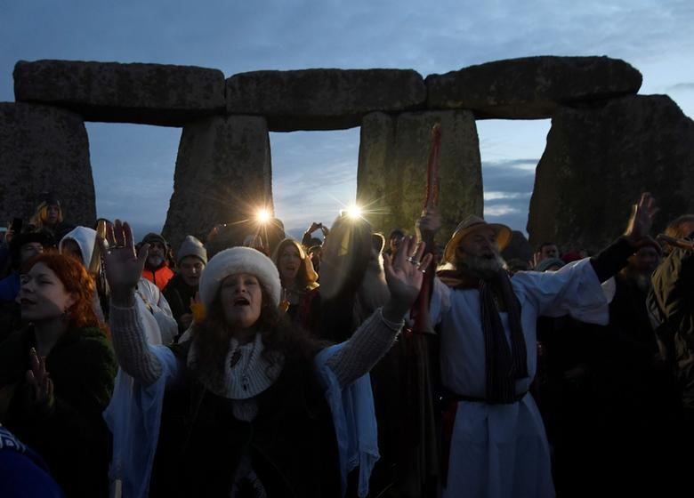 Visitors and revelers gather among the prehistoric stones of Britain's Stonehenge monument at dawn on winter solstice, the shortest day of the year. December 21, 2016.  REUTERS/Toby Melville