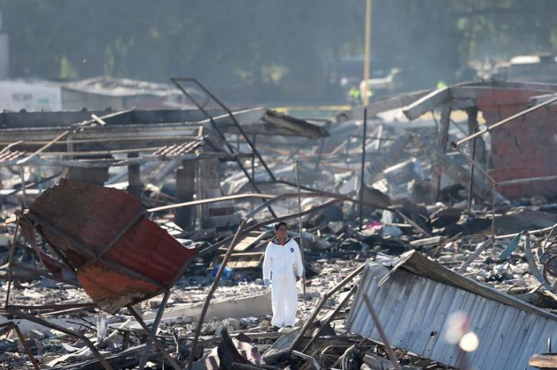 An investigator stands amidst the wreckage of houses destroyed in an explosion at the San Pablito fireworks market outside the Mexican capital, in Tultepec, Mexico December 21, 2016. REUTERS/Edgard Garrido