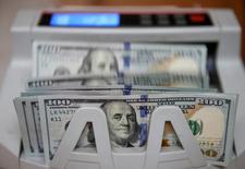 Доллары США в машине для счета денег. Доллар потерял часть преимущества в четверг, отойдя от максимума 14 лет к корзине валют, поскольку инвесторы фиксировали прибыль перед выходом множества экономических данных. REUTERS/Valentyn Ogirenko