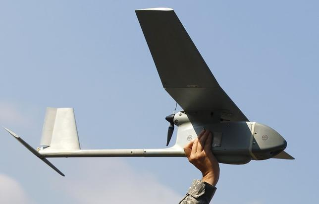 U.S. soldier Randell Atkinson poses in the starting position with a 'Raven' drone during its official presentation by the German and U.S. Unmanned Aerial Systems (UAS) at the U.S. military base in Vilseck-Grafenwoehr October 8, 2013.     REUTERS/Michaela Rehle