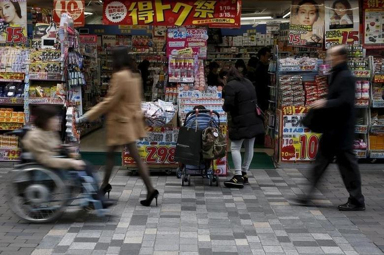 A woman with a baby buggy looks at items outside a discount store at a shopping district in Tokyo, Japan, February 25, 2016. REUTERS/Yuya Shino