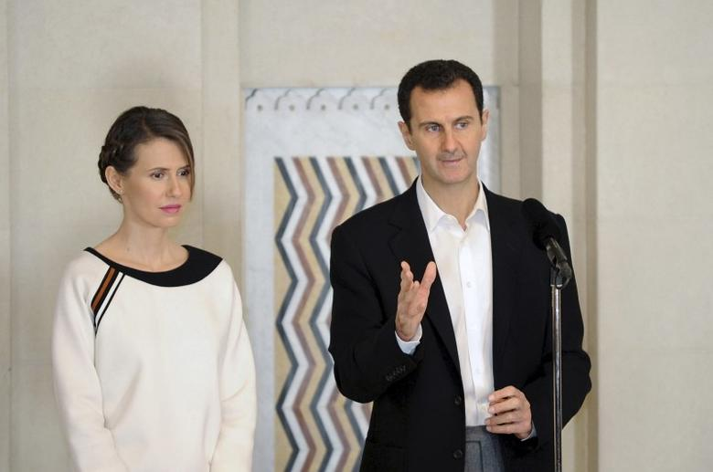 Syria's President Bashar al-Assad stands next to his wife Asma, as he addresses injured soldiers and their mothers during a celebration marking Syrian Mother's Day in Damascus, in this handout picture provided by SANA on March 21, 2016. SANA/Handout via REUTERS /Files
