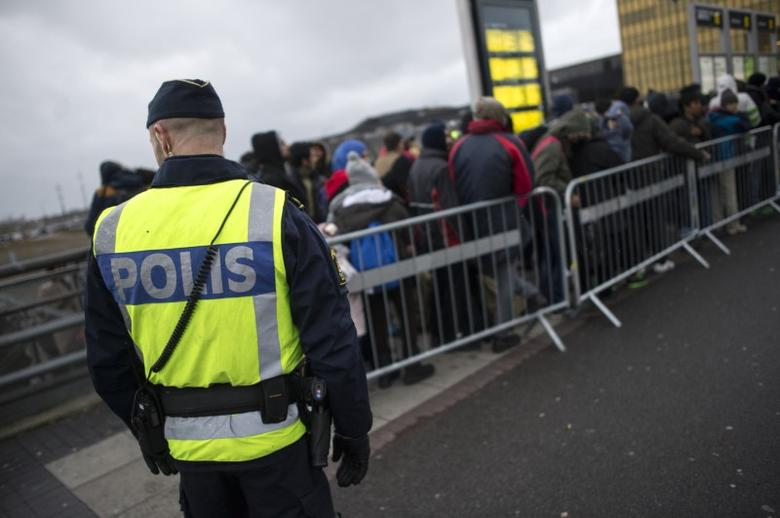 A police officer keeps guard as migrants arrive at Hyllie station outside Malmo, Sweden. Picture taken November 19, 2015. REUTERS/Johan Nilsson/TT NEWS AGENCY