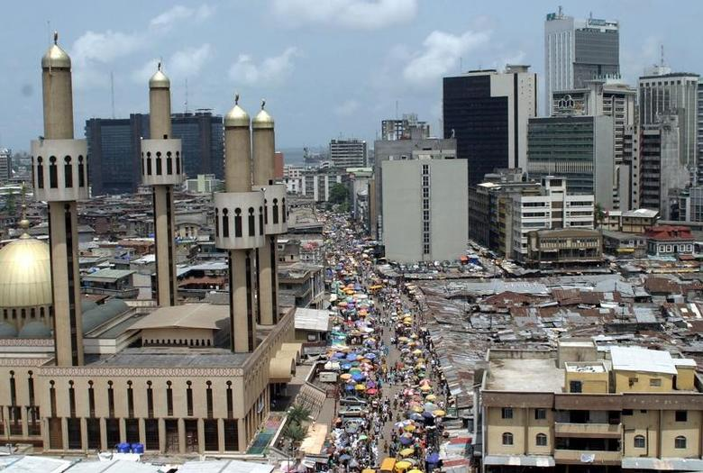 People and traffic move along a busy street in Lagos, Nigeria, May 24,2005. REUTERS/George Esiri