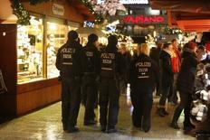 Полиция патрулирует вновь открывшийся рождественский рынок в Берлине. Камеры видеонаблюдения засняли тунисца, подозреваемого в осуществлении атаки на рождественском базаре в Берлине, через несколько часов после нападения, и следователи считают, что он все еще скрывается в немецкой столице, сообщили СМИ в пятницу.    REUTERS/Fabrizio Bensch