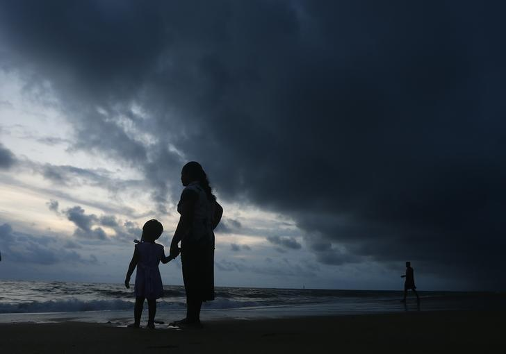 A mother holds her daughter's hand while they stand barefoot on a beach as rain clouds are seen over them in Colombo May 4 ,2014. REUTERS/Dinuka Liyanawatte/Files