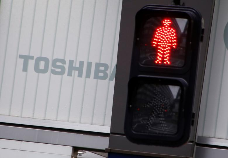 Toshiba's logo is seen behind a traffic sign at an electronic shop in Tokyo, Japan, November 11, 2016. REUTERS/Kim Kyung-Hoon/Files