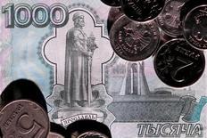 Монеты на 1000-рублевой купюре. 7 июня 2016 года. Рубль на торгах вторника показывал позитивную динамику в преддверии уплаты налога на прибыль и на фоне возобновления роста нефти после длинного уикенда, при этом активность участников рынка и объемы сделок по-прежнему ниже средних значений в преддверии новогодних праздников. REUTERS/Maxim Zmeyev/Illustration