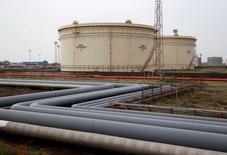 Нефтехранилища на НПЗ Essar Oil в Вадинаре, Индия. Цены на нефть немного снизились на спокойных торгах в среду, так как внимание рынка приковано к реализации соглашения ОПЕК и не входящих в картель государств о сокращении добычи, вступающего в силу с 1 января.    REUTERS/Amit Dave/File Photo