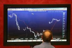 Трейдер изучает график торгов. Российские фондовые индексы в среду немного повысились при поддержке стабильно высоких цен на нефть и в отсутствие у инвесторов и трейдеров мотивации для торговли в оставшиеся до конца года несколько дней.     REUTERS/Alexander Natruskin