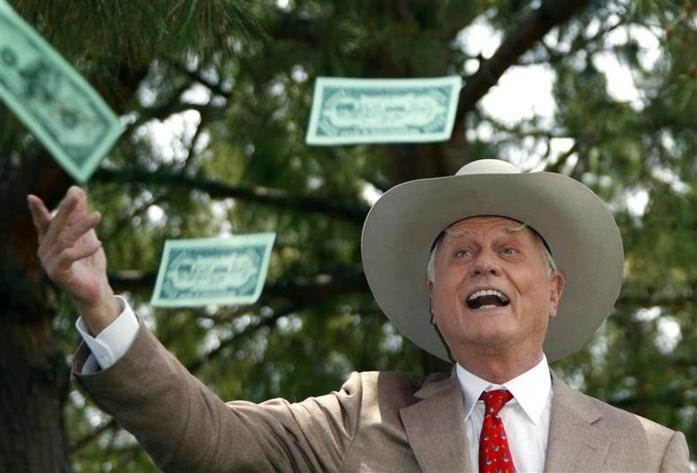 Actor Larry Hagman who played ''J.R. Ewing'' on television series ''Dallas'' throws fake dollars notes during a photocall at the 50th Monte Carlo television festival in Monaco June 8, 2010    REUTERS/Eric Gaillard