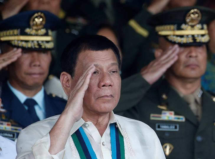 Philippine President Rodrigo Duterte salutes with other military officers during a anniversary celebration of the Armed Forces at a military camp in Quezon city, Metro Manila December 21, 2016. REUTERS/Erik De Castro