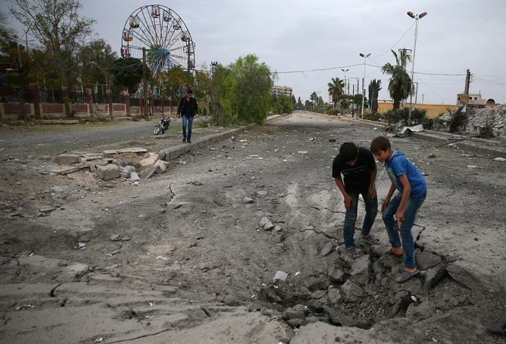 Boys inspect a hole in the ground after an airstrike near a playground on the besieged rebel held town of Douma, eastern Ghouta in Damascus, Syria, October 27, 2016. REUTERS/Bassam Khabieh/File Photo