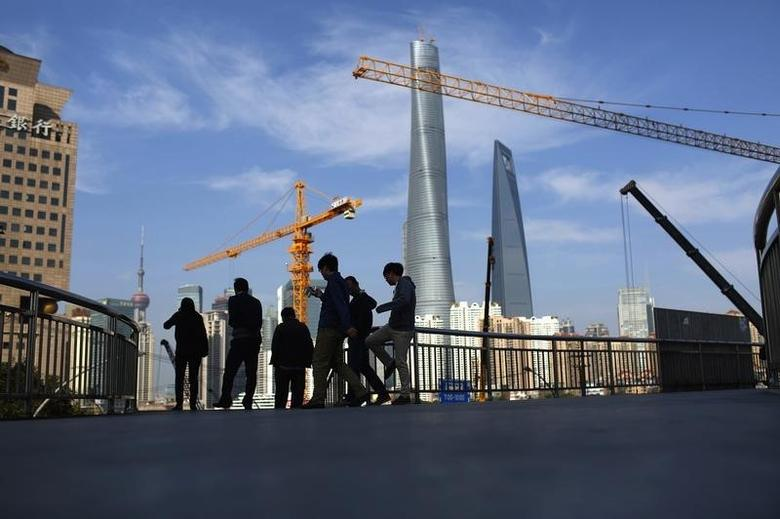People walk on a bridge near the financial district of Pudong in Shanghai November 21, 2014. REUTERS/Aly Song