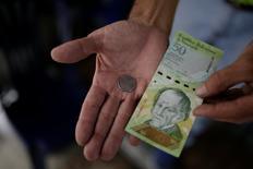 El presidente de Venezuela, Nicolás Maduro, anunció el jueves que postergó nuevamente la eliminación del billete de 100 bolívares, el de mayor denominación en el país, y cuyo primer intento de retirada este mes generó protestas y saqueos en la nación petrolera. Un comerciante sostiene una moneda de 50 bolívares y un billete de 50 bolívares para esta fotografía tomada en un puesto callejero en el centro de Caracas, el 29 de diciembre de 2016. REUTERS/Marco Bello