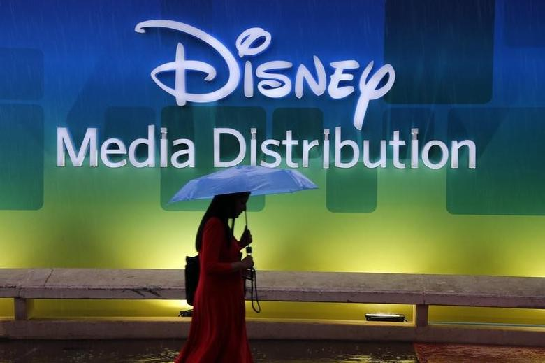 A visitor walks past a poster of Disney Media Distribution (DMD) during the annual MIPCOM television programme market in Cannes, southeastern France, October 13, 2014.   REUTERS/Eric Gaillard