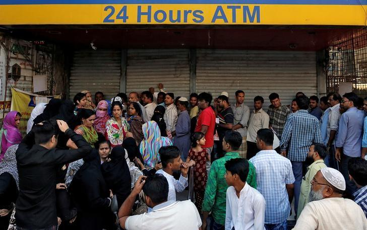People queue outside a bank to withdraw cash and deposit their old high denomination banknotes in Mumbai, India, December 2, 2016. REUTERS/Danish Siddiqui/File Photo