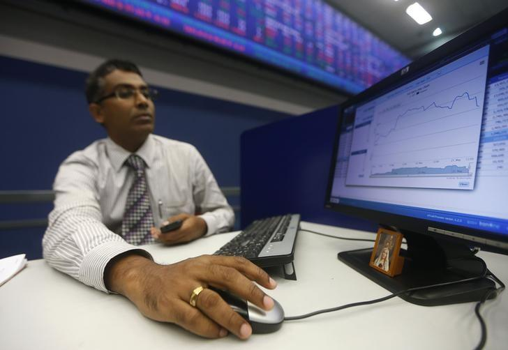 A broker looks at a computer screen showing the movement of the market since the morning opening, at the Colombo Stock Exchange in Colombo May 21, 2014. REUTERS/Dinuka Liyanawatte/File Photo