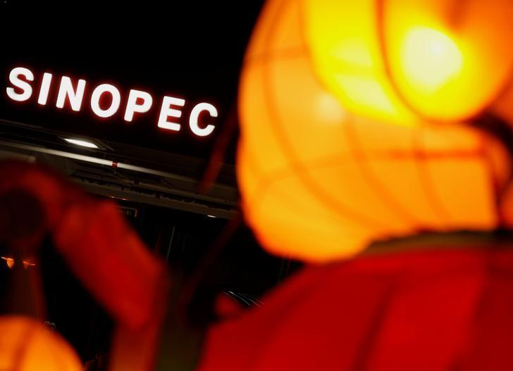 A Sinopec sign displayed at its gas station is seen behind a Chinese New Year lantern installation in Hong Kong February 5, 2013.  REUTERS/Bobby Yip/File Photo