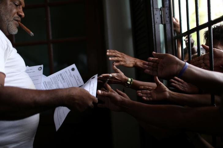 Followers of the Yoruba religion receive a sheet of paper with recommendations based on their annual predictions for the New Year, after a news conference in Havana, Cuba, January 3, 2017. REUTERS/Alexandre Meneghini