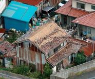 Des maisons endommagées par un tremblement de terre à Kurayoshi au Japon. Les assureurs ont versé environ 50 milliards de dollars (48 milliards d'euros) pour des sinistres liés à des catastrophes naturelles l'an dernier, soit près du double des 27 milliards de dollars de 2015, a annoncé mercredi le réassureur allemand Munich Re. /Photo prise le 21 octobre/REUTERS