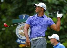 Tiger Woods of the U.S. lets go of his club after his tee shot on the seventh hole during the first round of the 2014 PGA Championship at Valhalla Golf Club in Louisville, Kentucky, August 7, 2014. REUTERS/Brian Snyder/File Photo