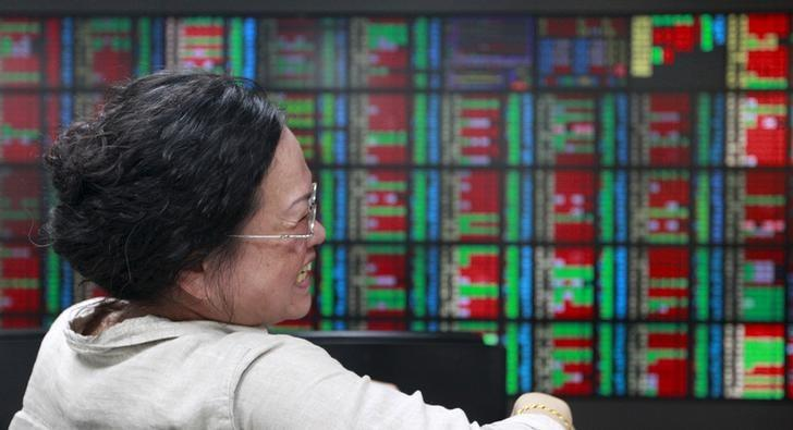A woman laughs while monitoring stock market prices inside a brokerage in Taipei, Taiwan, April 24, 2015.  REUTERS/Pichi Chuang/Files