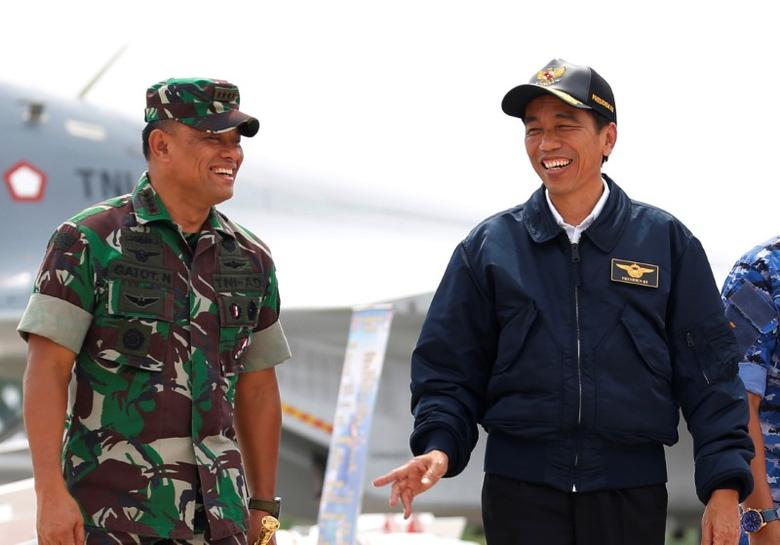 Indonesia's President Joko Widodo (R) talks with military Chief Gatot Nurmantyo as walk past fighter jets and weapons during a military exercise on Natuna Island, Riau Islands province, Indonesia October 6, 2016. Picture taken October 6, 2016. REUTERS/Beawiharta