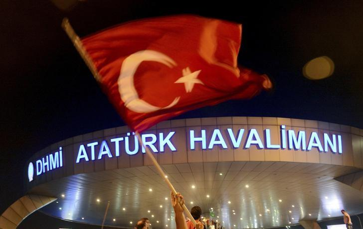 A man waves a Turkish flag in front of Ataturk Airport during an attempted coup in Istanbul, Turkey July 16, 2016. REUTERS/IHLAS News Agency