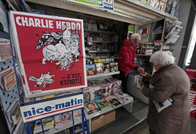 The front page of the new issue of satirical French weekly Charlie Hebdo entitled ''C'est Reparti'' (''Here we go again''),  is displayed at a kiosk in Nice February 25, 2015. REUTERS/Eric Gaillard/Files