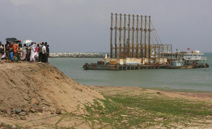 A group of Sri Lankan visitors at the new deep water shipping port watch Chinese dredging ships work in Hambantota, 240km (149 miles) southeast of Colombo, March 24, 2010. REUTERS/Andrew Caballero-Reynolds/File Photo