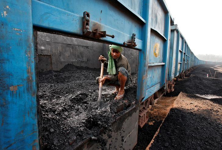 A worker unloads coal from a goods train at a railway yard in the northern city of Chandigarh, India, July 8, 2014. REUTERS/Ajay Verma/Files