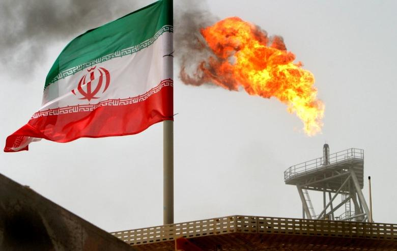 A gas flare on an oil production platform in the Soroush oil fields is seen alongside an Iranian flag in the Persian Gulf, Iran, July 25, 2005. REUTERS/Raheb Homavandi/File Photo