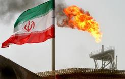 Una llamarada desde una plataforma de petroleo es visto junto a una bandera iraní en el Golfo Persa, Irán. 25 de julio 2005. Irán ha vendido más de 13 millones de barriles de petróleo que mantuvo por mucho tiempo en tanqueros en el mar, capitalizando el acuerdo de recorte de producción de la OPEP, del que está exento, para recuperar cuota de mercado y conseguir nuevos clientes, según fuentes y datos de la industria. REUTERS/Raheb Homavandi/File Photo