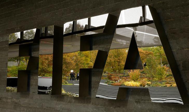 A TV team is reflected in a logo of FIFA a meeting of the FIFA Council at its headquarters in Zurich, Switzerland October 13, 2016.  REUTERS/Arnd Wiegmann/Files