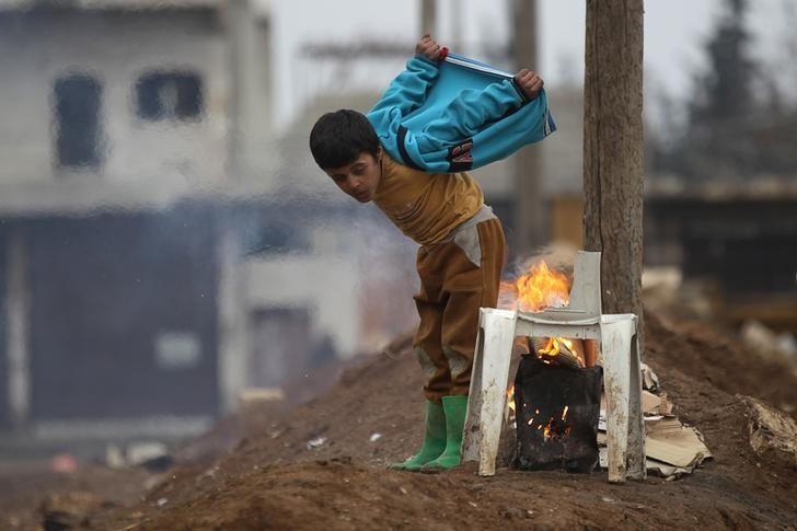 A boy warms himself around a fire in the northern Syrian rebel-held town of al-Rai, Syria January 5, 2017. REUTERS/Khalil Ashawi