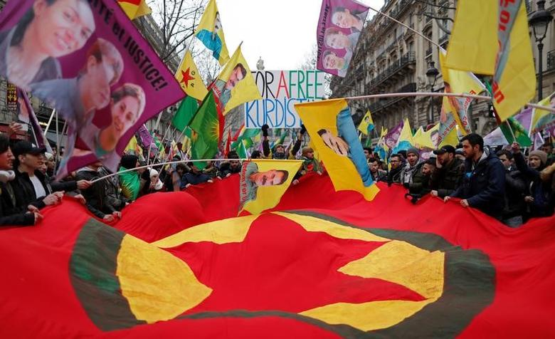 Members of the Kurdish community hold banner and flags during a gathering in tribute to Kurdish women, Fidan Dogan, Leyla Soeylemez and Sakine Cansiz in front of the Gare du Nord railway station in Paris, France, January 7, 2017. REUTERS/Christian Hartmann