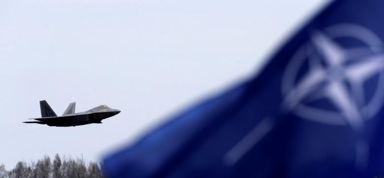 NATO flag flutters as U.S. Air Force F-22 Raptor fighter flies over the military air base in Siauliai, Lithuania, April 27, 2016. REUTERS/Ints Kalnins/Files