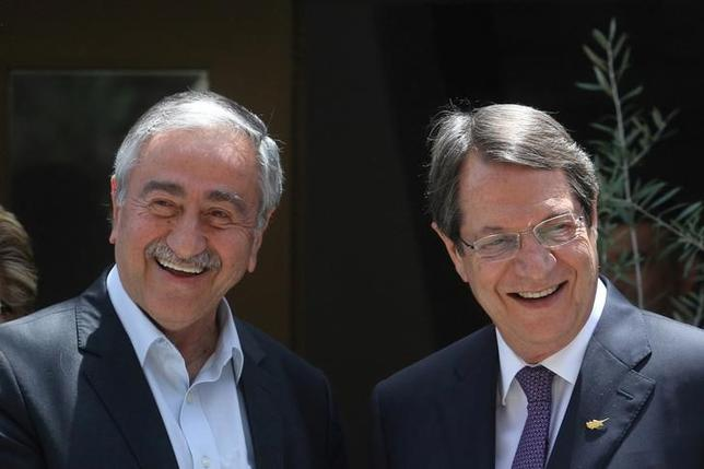 Greek Cypriot leader and Cyprus President Nicos Anastasiades (R) and Turkish Cypriot leader Mustafa Akinci smile during an event organized by the Bi-communal Technical Committee on Education in Nicosia, Cyprus June 2, 2016. REUTERS/Yiannis Kourtoglou/Files