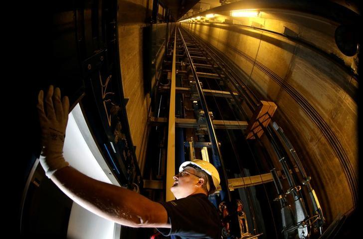 A service engineer of Germany's industrial conglomerate ThyssenKrupp AG inspects the door inside an elevator shaft at an office building in Berlin, Germany September 17, 2013. REUTERS/Tobias Schwarz/File Photo