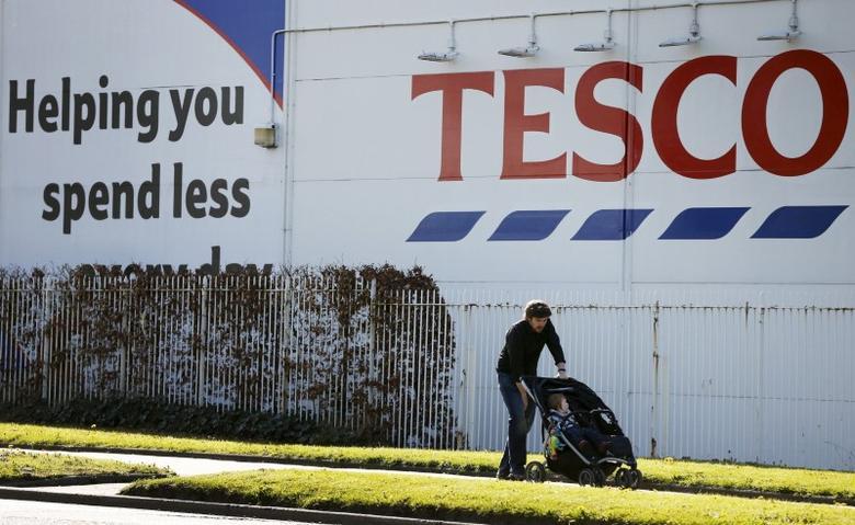 A man pushes a pram past a Tesco supermarket near Altrincham, northern England, April 22, 2015.  REUTERS/Phil Noble