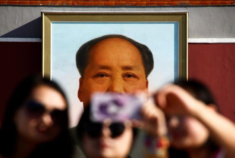 People take pictures on Tiananmen Square as the portrait of China's late Chairman Mao Zedong is seen in the background in Beijing, China, on the 40th anniversary of his death September 9, 2016. REUTERS/Thomas Peter