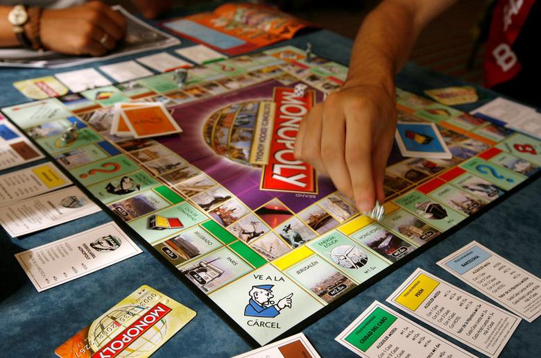 Players participate in a world record attempt by Monopoly enthusiasts across the world to set a Guinness world record for the largest simultaneous game of Monopoly, at a hotel in Madrid, August 27, 2008. REUTERS/Paul Hanna/File Photo