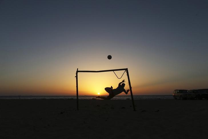 A boy jumps to save a goal while playing soccer on the beach in Benghazi June 1, 2014. REUTERS/Esam Omran Al-Fetori